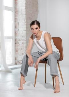 밝은 스튜디오에서 탱크 탑과 회색 바지를 입고 포즈를 취하는 우아한 여성 모델. 새로운 여성 개념