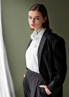 Elegant female model posing in a jacket suit with a tie. new feminity concept