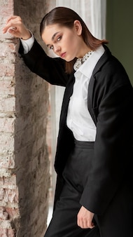 Elegante modello femminile in posa in un completo giacca con cravatta. nuovo concetto di femminilità