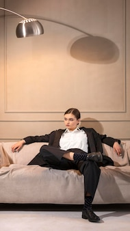 Elegante modello femminile in posa in un divano in giacca e cravatta. nuovo concetto di femminilità