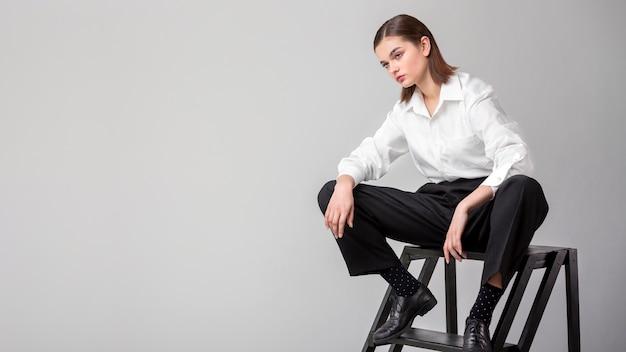 Elegante modello femminile in posa per le scale in un abito giacca. nuovo concetto di femminilità