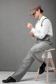 Elegante modello femminile in posa in uno sgabello in elegante camicia bianca e bretelle. nuovo concetto di femminilità