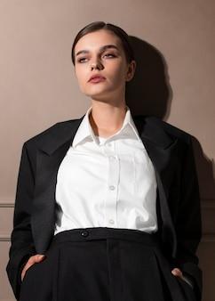 Elegante modello femminile in posa in studio in giacca e cravatta. nuovo concetto di femminilità