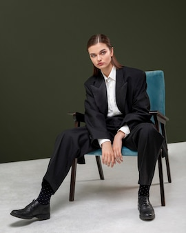 Elegant female model sitting in an armchair in a jacket suit. new feminity concept