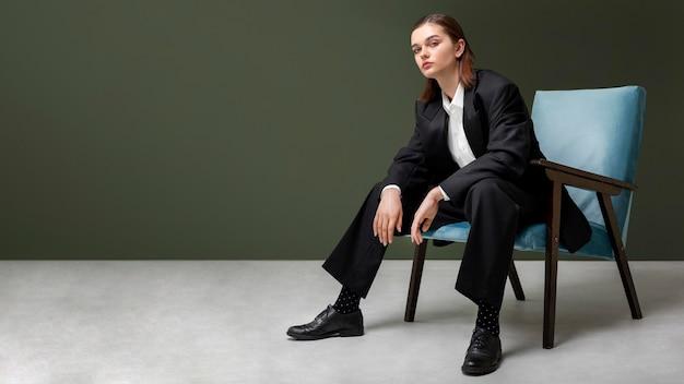 재킷 정장에 안락의 자에 앉아 우아한 여성 모델. 새로운 여성 개념