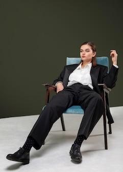 ジャケットスーツの肘掛け椅子に座っているエレガントな女性モデル。新しい女性らしさの概念
