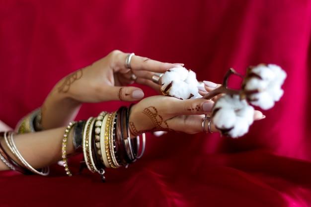 Элегантные женские запястья расписаны хной с традиционными индийскими восточными орнаментами менди. руки, одетые в браслеты и кольца, держат ветку с хлопковыми цветами. бордовая ткань с складками на фоне.