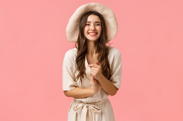 Elegant and feminine beautiful young woman clasp hands and smiling as enjoying nice casual conversation with group friends, shopping, smiling and laughing enthusiastic, pink wall