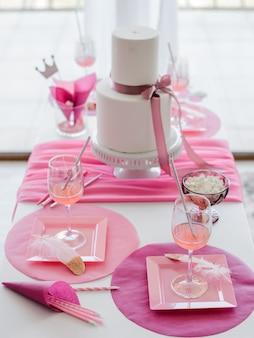 ピンクのナプキンと皿を配した明るい色調のエレガントなお祝いテーブルセッティング。結婚式、誕生日、ベビーシャワー、女の子のパーティーの装飾。