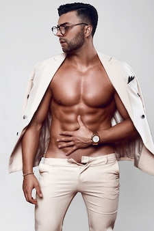 Elegant fit brutal man model in a light suit and glasses