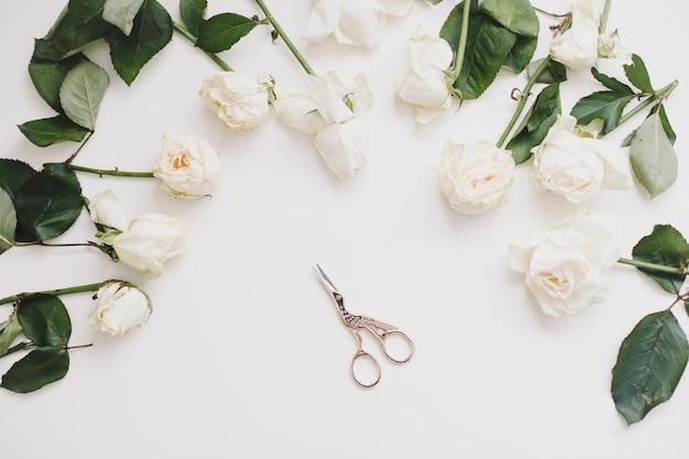 Элегантная цветочная композиция с белыми розами и ножницами на белом. flatlay, вид сверху