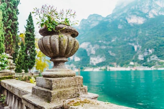 Elegant flower pots decorate the classic stone railing on a romantic walk by a lake in riva del garda.