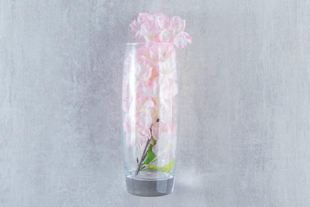 白いテーブルの上に、水差しのエレガントな花。