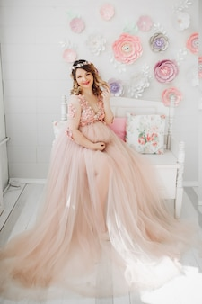 Elegant future mother posing in long dress