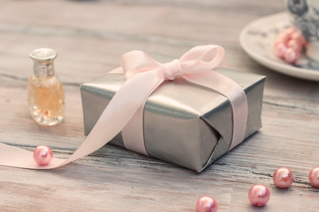 Elegant gift box in silver paper with a pink ribbon and perfume
