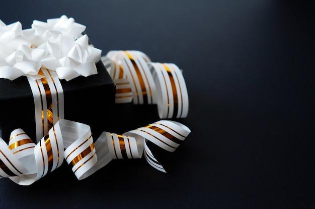Elegant gift box wrapped in white striped ribbon on black textured background.
