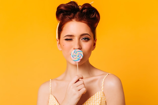 Elegant ginger girl licking lollipop. front view of enthusiastic woman with hard candy.