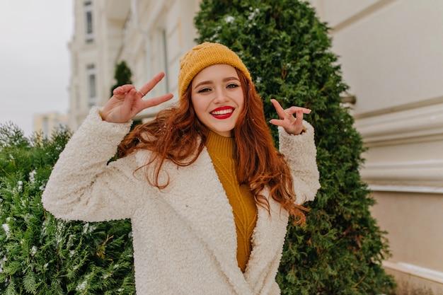 冬を楽しんでいるエレガントな生姜の若い女性。屋外のピースサインでポーズをとって喜んで赤毛の女の子。
