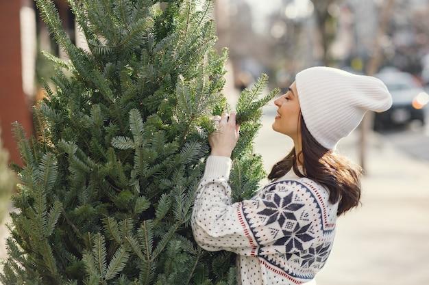 エレガントな女の子がクリスマスツリーを購入します。