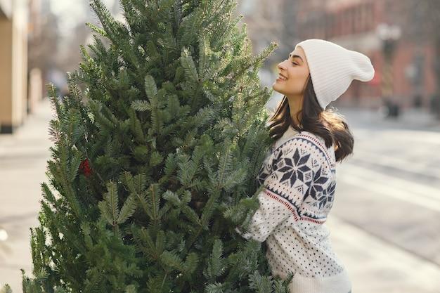 우아한 소녀는 크리스마스 트리를 구입합니다.