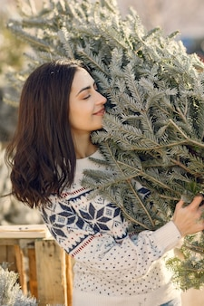 Элегантная девушка покупает елку.