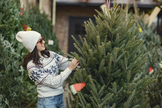 La ragazza elegante acquista un albero di natale.