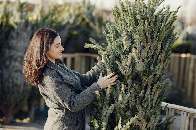 Elegant girl buys a christmas tree.