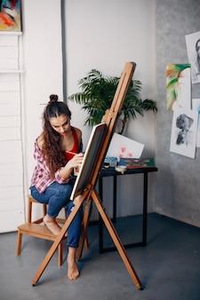 Elegant girl draws in an art studio