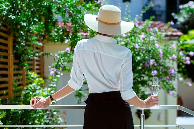 챙이 넓은 모자를 쓴 우아한 소녀가 시골집 테라스에 들어와 정원을 바라보고 있습니다. 휴식, 휴식의 개념입니다. 피크닉, 캠핑장. 혼합 매체