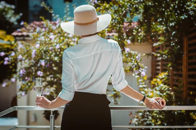 Элегантная девушка в широкополой шляпе вышла на террасу загородного дома и смотрит в сад.