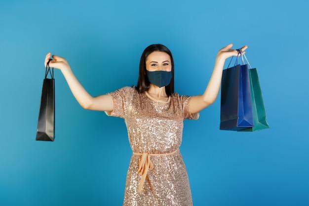 드레스를 입은 우아한 소녀가 코로나 바이러스 covid 19 예방을위한 보호 마스크로 쇼핑합니다.
