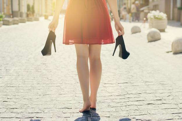 Элегантная девушка в красном платье с высокими каблуками в руках, босиком идет по улице. закройте обрезанное сзади фото заднего вида. луч солнца световые лучи сияют солнечные лучи всплеск блестящий эффект вспышки блики блеск