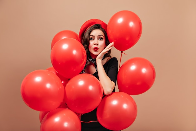 Elegant girl in red beret and black dress blows kiss and holds huge balloons.
