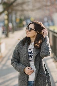 優雅な女の子は冬の街を歩きます。