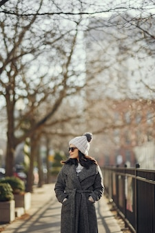Ragazza elegante a piedi in una città invernale.