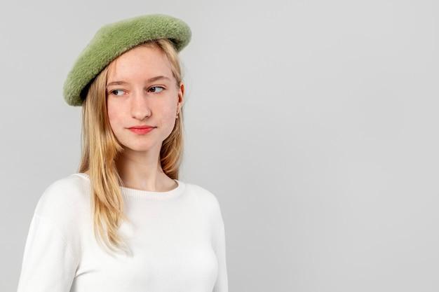 緑のベレー帽を身に着けているエレガントな女の子