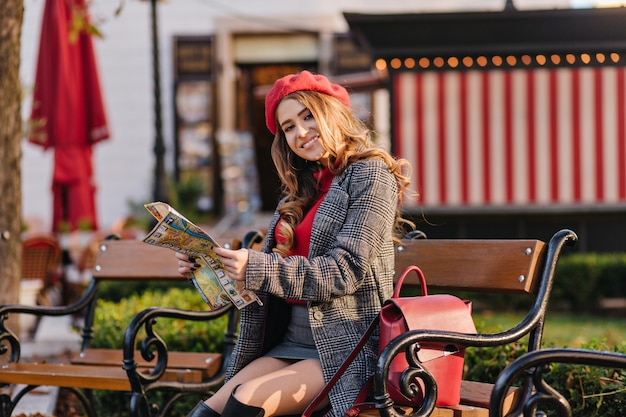 Elegant girl wears skirt and beret sitting on wooden bench in warm autumn day and holding newspaper