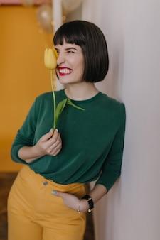 エレガントな女の子は、チューリップでポーズをとっている間、変な顔をする黄色いズボンを着ています。花を持って笑っている赤い唇を持つ見事なブルネットの女性。