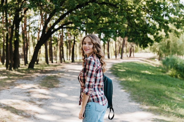 肩越しに見て、公園で散歩を楽しんでいる巻き毛の髪型を持つエレガントな女の子。自然にポーズをとるカジュアルな服装で気さくな女性。