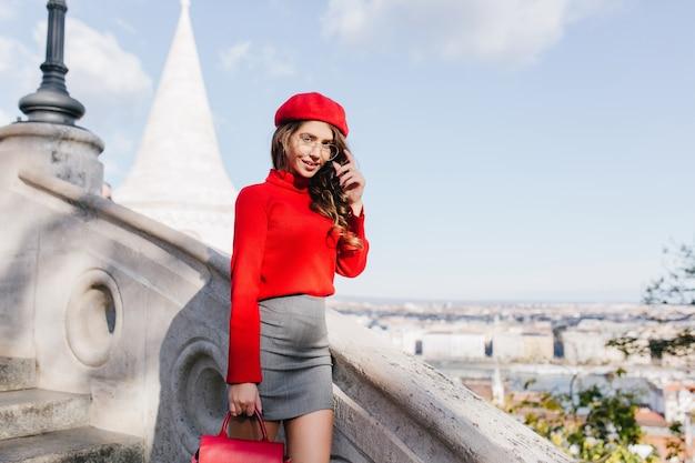 Elegante ragazza con piccola borsa in pelle che guarda con interesse alla telecamera sullo sfondo del cielo