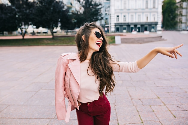 Elegant girl with long hairstyle in vinous pants having fun in city. she has pink jacket on shoulder, showing to side.