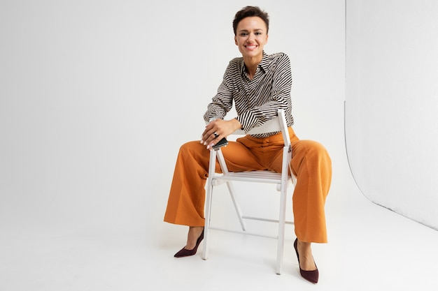 Elegant girl with a short haircut in classic pants and a shirt posing sitting on chair on white