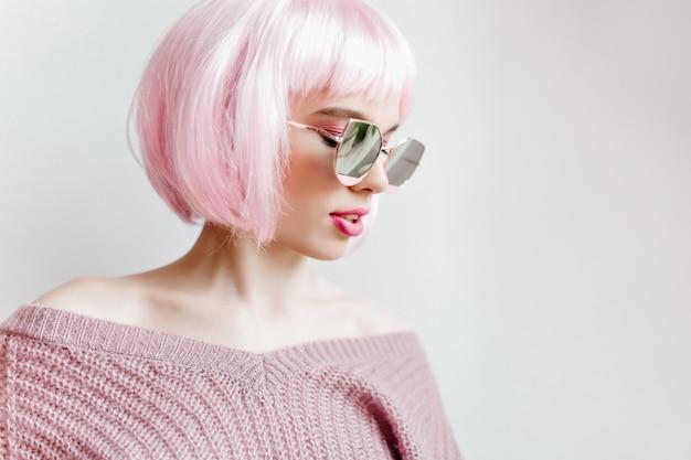 Элегантная девушка с короткими розовыми волосами наслаждается модной фотосессией на светлой стене. чудесная белая дама в парике и фиолетовом свитере.