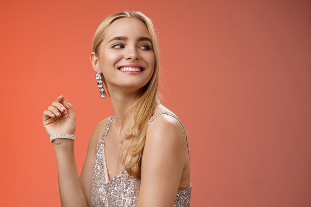 Элегантная гламурная великолепная молодая богатая блондинка посещает благотворительную вечеринку в стильном серебряном блестящем платье с аксессуарами, поворачивая направо, улыбаясь приветствуя знакомого человека, радостно улыбающегося, красный фон.