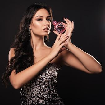 Элегантная гламурная женщина в красивом платье с духами
