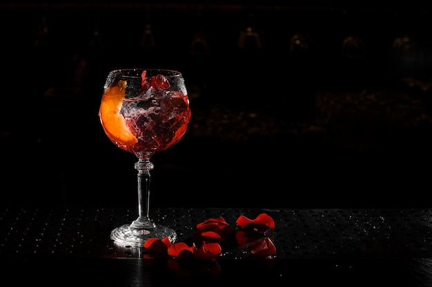 Elegant glass filled with fresh and tasty aperol syringe summer cocktail on the black background