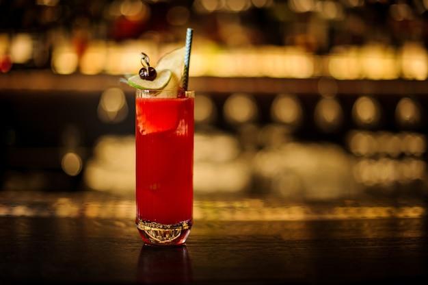 Элегантный бокал красного сладкого сочного напитка в коктейльном бокале, украшенном фруктами и соломинкой