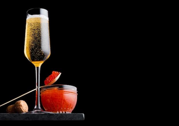 赤キャビアと黄色のシャンパンのエレガントなガラス Premium写真