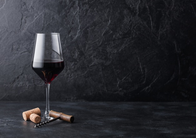 Elegant glass of red wine with corks and corkscrew on black stone background.