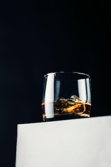 Elegant glass of whiskey with ice cubes on a white stand